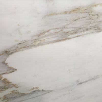 Piedra natural mármol con vetas grises y doradas CALACATTA